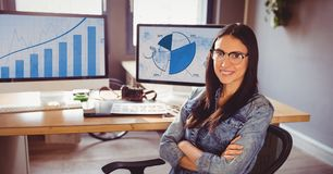 Woman in spectacles sitting on her desk with arms crossed. At office Stock Photography