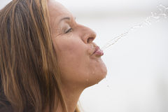 Woman spewing water for fun refreshment Stock Images