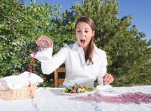 Woman spilling wine. Trying to pick the glass and making things just worse Royalty Free Stock Images