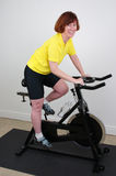 Woman on Spinning bike. Woman working out on a spinning bike in a home gym Royalty Free Stock Images