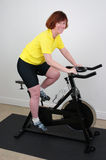 Woman on Spinning bike. Woman working out on a spinning bike in a home gym Royalty Free Stock Photos