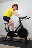 Woman on Spinning bike. Woman working out on a spinning bike in a home gym Stock Photo