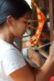 Woman spinning bright orange silk Stock Image
