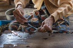 Woman spinning a lotus flower. Detail of the hands of an elderly woman in traditional dress spinning a lotus flower. On Inle Lake stock images