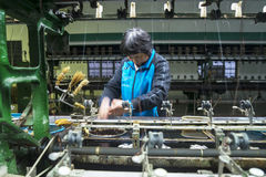Woman with spinning machine of silk cocoons Stock Photography