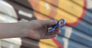 A woman spinning a spinner on a background of graffiti. stock footage
