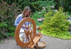 Woman Spinning Wool. This pretty woman is hand spinning wool on a wheel in motion in a pretty peaceful garden setting as her home business Royalty Free Stock Images