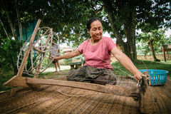 Woman spins cotton thread. Royalty Free Stock Images