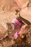 Woman Splashes Muddy Water At Dirty Girl Mud Run Event. Hampton, GA, USA - April 23, 2016: A woman splashes muddy water as she lands in a mud pit at the Dirty stock images