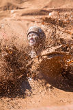 Woman Splashes Muddy Water In Dirty Girl Mud Run. Hampton, GA, USA - April 23, 2016: A woman creates a big splash of muddy water as she lands in a mud pit at the royalty free stock photography