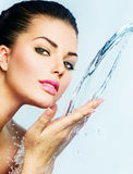 Woman with splashes of water. Beautiful woman with splashes of water in her hands Stock Images