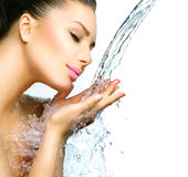 Woman with splashes of water in her hands Stock Image