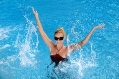 Woman splashing in the pool Stock Photo