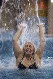 Woman splashing in a pool under jet of water Stock Photography