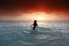 Woman splashing in sea on sunset Stock Image