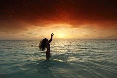 Woman splashing in sea on sunset Royalty Free Stock Image