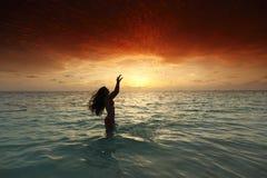 Woman splashing in sea on sunset Royalty Free Stock Image