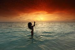 Woman splashing in sea on sunset Royalty Free Stock Photos