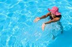 Woman splashing in swimming pool Stock Photos