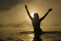 Woman splashing in water Stock Photo
