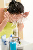 Woman splashing water on face in bathroom Royalty Free Stock Images