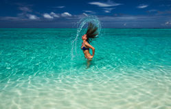 Woman splashing water with hair in the ocean Royalty Free Stock Image