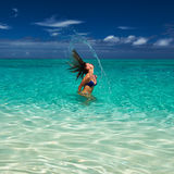 Woman splashing water with hair in the ocean Royalty Free Stock Photography