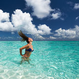 Woman splashing water with hair in the ocean Royalty Free Stock Photos