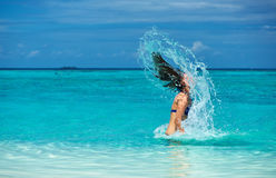 Woman splashing water with hair in the ocean Royalty Free Stock Photo