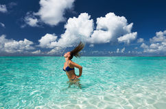 Woman splashing water with hair in the ocean Stock Photo