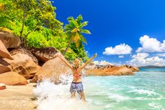 Woman splashing wave Seychelles. Funny tourist woman in splashing wave at Felicite Island, La Digue. Tropical jungle landscape of Seychelles. Granite boulder royalty free stock photos