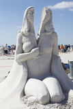 Woman split into two parts. It's amazing what sandsculpting artists can do! The whole figure is made ouot of sand stock photography