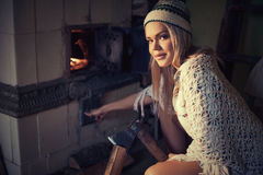 Woman spliting logs and burning wood in stove at home. Young blonde woman spliting logs and burning wood in stove at home Stock Photo