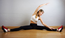 Woman - Splits and Stretch. Middle aged woman in white tanktop and black leggings doing exercise. Stretches inner thighs and right side, White brick wall and stock photo