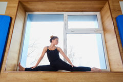 Woman on the splits in the window at the gym. Stock Photo