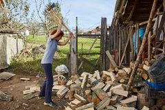 Woman splitting wood. Woman with an ax splitting beech logs for firewood Stock Photo