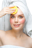 Woman with sponge cleaning her face Royalty Free Stock Images