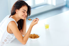 Woman with a spoon and a bowl of cereal looking down Stock Photo