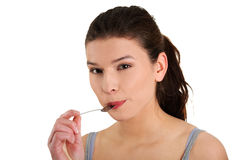 Woman with spoon in her mouth Stock Images