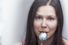 Woman with a spoon in a mouth Stock Photos