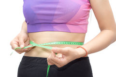 Woman in sport bra measuring her body with tape isolated on whit Stock Images