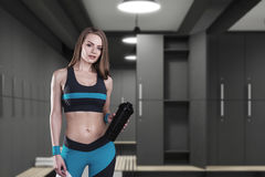 Woman in sport clothes in locker room. Beautiful woman in sportswear is holding a bottle and standing in a gray locker room with benches. 3d rendering mock up Royalty Free Stock Image