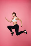 Woman in sport clothing pretends running in air jumping high Royalty Free Stock Photos