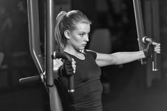 Woman at the sport gym doing arms exercises on a machine Stock Photography
