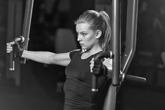 Woman at the sport gym doing arms exercises on a machine. Black and white sport club Stock Photo