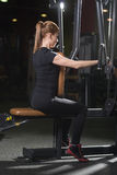 Woman at the sport gym doing arms exercises on a machine Royalty Free Stock Photography
