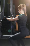 Woman at the sport gym doing arms exercises on a machine Royalty Free Stock Images