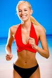 Woman in sport-wear on beach. Young attractive happy smiling blond woman in sport wear running on sea beach Stock Photos