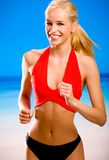 Woman in sport wear running. Young attractive happy smiling blond woman in sport wear running on sea beach Royalty Free Stock Images