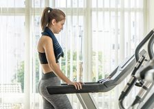 Woman in sport wear starting her run on treadmill. Woman in sport wear starting her run on a treadmill Royalty Free Stock Photo